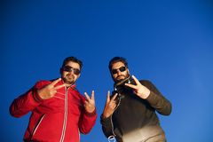 Two men wearing black sunglasses showing victory sign by hands. Two young guy wearing sunglasses standing and showing victory sign by hands unique photo stock photo