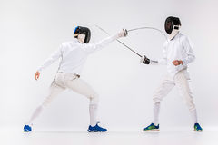 The two men wearing fencing suit practicing with sword against gray. Studio background Stock Photography
