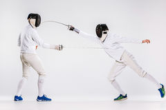 The two men wearing fencing suit practicing with sword against gray Royalty Free Stock Images