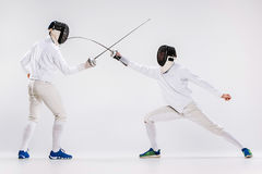 The two men wearing fencing suit practicing with sword against gray Stock Photos