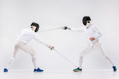 The two men wearing fencing suit practicing with sword against gray Royalty Free Stock Image