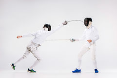 The two men wearing fencing suit practicing with sword against gray Stock Photography