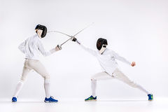The two men wearing fencing suit practicing with sword against gray. Studio background Royalty Free Stock Photos