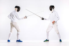 The two men wearing fencing suit practicing with sword against gray. Studio background Royalty Free Stock Images