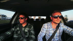 Two men wearing sunglasses in the car, start to drive. In full HD stock footage