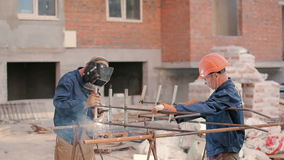 Two men welding a pipe at the construction. One of the workers hold a construction. Other man in helmet welding a pipe to the construction stock video