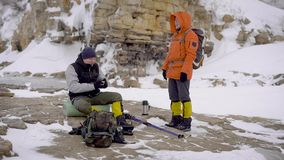 Two men went on a winter hike. Friends have professional equipment, they walk along the cliff. Extreme winter holiday stock video
