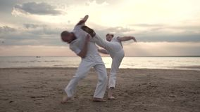 Two men practicing capoeira on beach. Two men in white clothes practicing capoeira on beach stock footage