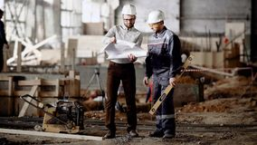 Two men in white safety hardhats standing in building site. Engineer bringing contsruction plan and showing it to worker. Two men in safety hardhats are meeting stock video