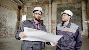 Two men, who builders in a protective helmet on their heads and special clothes look at the factory building in order to