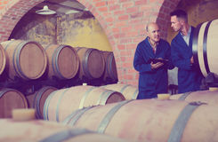 Two men winery employees writing note Royalty Free Stock Image