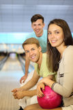 Two men and woman with ball sit in bowling club Stock Images
