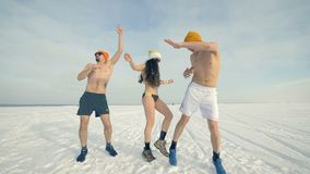 Two men and a woman in bikini dance on the snow. 4K. Two men and a woman in bikini dance on the snow stock footage