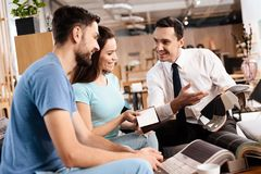 Two men and a woman are discussing the purchase of new furniture. Two men and a women are discussing the purchase of new furniture. This is a young family who Royalty Free Stock Photography