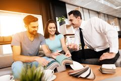 Two men and a woman are discussing the purchase of new furniture. Two men and a women are discussing the purchase of new furniture. This is a young family who Royalty Free Stock Photos