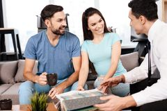 Two men and a woman are discussing the purchase of new furniture. Two men and a women are discussing the purchase of new furniture. This is a young family who Stock Image