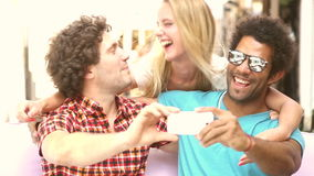Two men and woman having fun taking spontaneous selfies. Two young men and a blonde woman having fun and taking selfies in town, graded brighter stock video footage