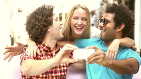 Two men and woman having fun taking spontaneous selfies. Two young men and a blonde woman having fun and taking selfies in town, graded brighter stock video