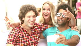 Two men and woman having fun taking spontaneous selfies. Two young men and a blonde woman having fun and taking selfies in town, graded brighter stock footage