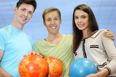 Two men and woman hold balls in bowling club Royalty Free Stock Images