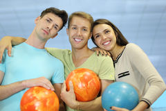 Two men and woman hold balls in bowling club Stock Image