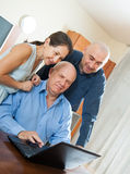 Two men and woman at home online Stock Image