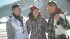 Two Men and Woman are Hugging Each Other Standing Outside During Warm Winter Day in the Mountains. One Man is Holding stock video