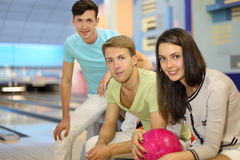 Two men and woman sit in bowling club. Two men and women sit in bowling club; women holds pink ball; focus on center man; shallow depth of field Stock Photography