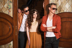 Two men and woman standing at the door. Blond and brunet young men in sunglasses and women with long curly hair standing at the door Stock Image