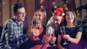 Two men and women enjoying some Christmas wine. Two men and two women in close view talking and holding wine glasses near a Christmas tree stock video footage