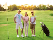 People playing golf. Two men and a women are holding golf clubs, looking at camera and smiling while standing on golf course Stock Photo
