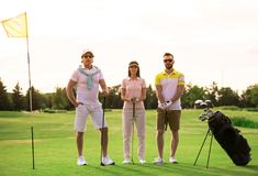 People playing golf. Two men and a women are holding golf clubs and looking at camera while standing on golf course Royalty Free Stock Photo