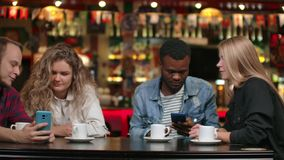 Two men and two women multi-ethnic couples sit in a cafe and look at the screens of smartphones and discuss.  stock footage