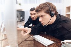 Two men work as guards. They sit in front of the monitors in the security room. The headphones are on their heads. They are photographed through the glass Royalty Free Stock Images