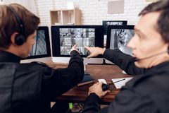 Two men work as guards. They sit in front of the monitors in the security room. The headphones are on their heads Stock Image