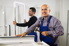 Two men work at PVC windows factory. Two careful workmen work at PVC windows factory stock images