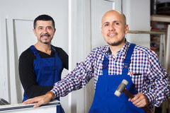 Two men work at PVC windows factory. Two happy men work at PVC windows factory royalty free stock images