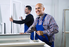 Two men work at PVC windows factory. Two positive workmen work at PVC windows factory stock image
