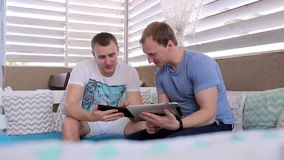 Two men work with tablets in a cafe. Two men met in a cafe to discuss matters stock video footage