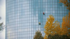 Two men workers cleaning the exterior windows of a skyscraper - industrial alpinism