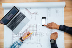 Two men working for blueprint using mobile phone and laptop Stock Images