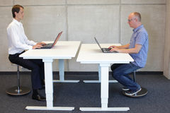 Two men working in correct sitting posture on pneumatic leaning seats. With laptops  at electric height adjustable desks in office Stock Images