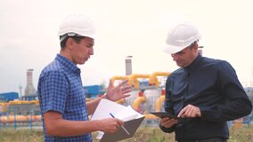 Two men working engineers work at a gas plant producing gas oil. industry business teamwork concept. Worker and engineer