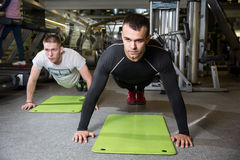 Two men working on exercise mat in fitness studio. Royalty Free Stock Image