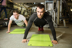 Two men working on exercise mat in fitness studio. Preparation o Stock Photography