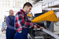 Two men working on machine. Two smiling men in uniform working on machine in PVC shop Stock Photo
