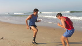 Two Men Working Out On Beach Together. Two men run on the spot before dropping and doing press ups on beach. Shot on Canon 5d Mk2 with a frame rate of 30fps stock video footage