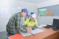 Two men working on scale drawings one sat on table. Men stock photo