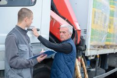 Two men working on truck. Two men working on a truck Royalty Free Stock Photos