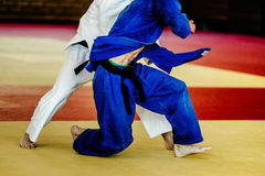 Two men wrestlers judoka. White and blue kimono on tatami fight Stock Images